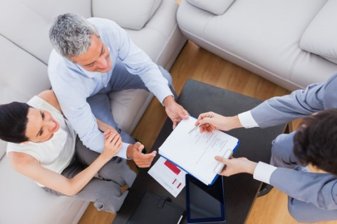 Mortgage broker explaining document to couple